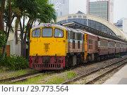 Пассажирский поезд на главном железнодорожном вокзале Хуа Лампхонг пасмурным днем. Бангкок, Таиланд (2019 год). Редакционное фото, фотограф Виктор Карасев / Фотобанк Лори