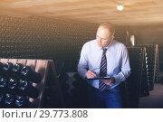 Wine producer with clipboard in wine cellar. Стоковое фото, фотограф Яков Филимонов / Фотобанк Лори