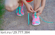 Hands of a young woman lacing bright pink and blue sneakers. Running shoes - closeup of woman tying shoe laces. Стоковое видео, видеограф Дмитрий Травников / Фотобанк Лори