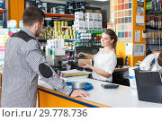 Купить «Female seller standing at the counter and consulting male», фото № 29778736, снято 17 мая 2018 г. (c) Яков Филимонов / Фотобанк Лори