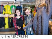 Купить «Guy and a girl are looking at a warm jacket», фото № 29778816, снято 8 марта 2017 г. (c) Яков Филимонов / Фотобанк Лори