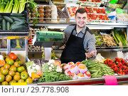 Купить «cheerful male seller showing assortment of grocery shop», фото № 29778908, снято 18 марта 2017 г. (c) Яков Филимонов / Фотобанк Лори