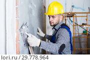 Купить «Smiling professional in the helmet is plastering the wall», фото № 29778964, снято 3 июня 2017 г. (c) Яков Филимонов / Фотобанк Лори