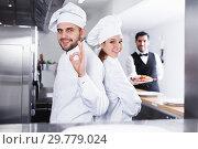 Купить «two chefs, standing back to back in kitchen», фото № 29779024, снято 26 января 2018 г. (c) Яков Филимонов / Фотобанк Лори