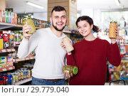 Купить «satisfied young family choosing purchasing canned food for week at supermarket», фото № 29779040, снято 14 марта 2017 г. (c) Яков Филимонов / Фотобанк Лори