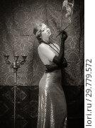 Купить «Girl in an evening dress with a cigarette mouthpiece. Studio portrait in retro style, toned in sepia», фото № 29779572, снято 27 декабря 2018 г. (c) Вадим Орлов / Фотобанк Лори