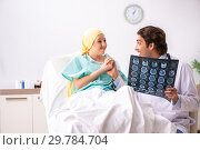 Купить «Young handsome doctor visiting female oncology patient», фото № 29784704, снято 3 октября 2018 г. (c) Elnur / Фотобанк Лори
