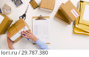 Купить «woman with parcels and clipboard at post office», видеоролик № 29787380, снято 19 января 2019 г. (c) Syda Productions / Фотобанк Лори