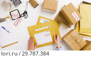 Купить «woman sticking fragile marks at post office», видеоролик № 29787384, снято 19 января 2019 г. (c) Syda Productions / Фотобанк Лори