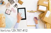 Купить «woman with tablet pc and clipboard at post office», видеоролик № 29787412, снято 19 января 2019 г. (c) Syda Productions / Фотобанк Лори