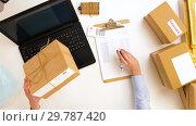Купить «woman with laptop and clipboard at post office», видеоролик № 29787420, снято 19 января 2019 г. (c) Syda Productions / Фотобанк Лори