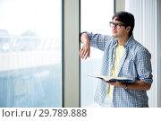 Купить «Young handsome student standing at the window», фото № 29789888, снято 2 августа 2018 г. (c) Elnur / Фотобанк Лори