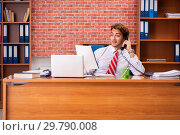 Купить «Young handsome employee sitting in the office», фото № 29790008, снято 1 сентября 2018 г. (c) Elnur / Фотобанк Лори