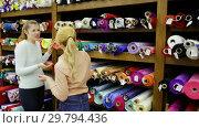 Купить «Portrait of two positive attractive girls choosing fabric among diversity on shelves in store», видеоролик № 29794436, снято 28 марта 2018 г. (c) Яков Филимонов / Фотобанк Лори