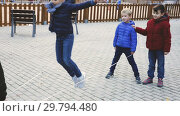 Купить «Happy kids skipping on chinese jump rope on playground in autumn day», видеоролик № 29794480, снято 18 декабря 2018 г. (c) Яков Филимонов / Фотобанк Лори