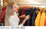 Купить «Young blonde woman choosing baby clothes small size in shop», видеоролик № 29794484, снято 13 ноября 2018 г. (c) Яков Филимонов / Фотобанк Лори