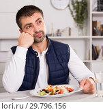 Купить «Sadly young man before eating vegetable salad from plato», фото № 29796156, снято 25 декабря 2017 г. (c) Яков Филимонов / Фотобанк Лори