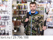 Купить «Fisherman in fishing clothing standing with fishing rod», фото № 29796188, снято 16 января 2018 г. (c) Яков Филимонов / Фотобанк Лори