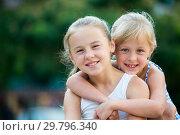 Купить «Two small happy sisters outdoors», фото № 29796340, снято 20 июля 2017 г. (c) Яков Филимонов / Фотобанк Лори