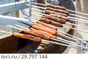 Купить «Tasty sausages cooking over the hot coals on a barbecue fire», фото № 29797144, снято 19 мая 2018 г. (c) FotograFF / Фотобанк Лори