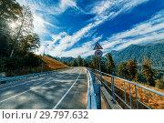 Купить «Asphalt mountain road. Blue sky with white clouds.», фото № 29797632, снято 15 августа 2015 г. (c) Андрей Радченко / Фотобанк Лори