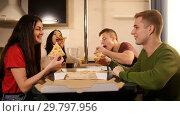 Купить «Company of four young friends sitting in kitchen and eating pizza», фото № 29797956, снято 22 февраля 2019 г. (c) Константин Шишкин / Фотобанк Лори