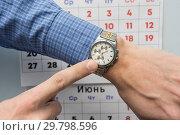 Купить «Рука офисного специалиста указывает на наручные часы, на заднем плане настенный календарь», фото № 29798596, снято 28 января 2019 г. (c) Иванов Алексей / Фотобанк Лори