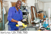 Купить «smiling African American glazier choosing glass for cutting in workshop», фото № 29798780, снято 16 мая 2018 г. (c) Яков Филимонов / Фотобанк Лори