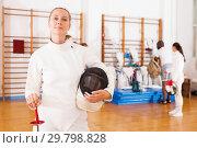 Купить «Sporty young woman in uniform standing at fencing workout», фото № 29798828, снято 11 июля 2018 г. (c) Яков Филимонов / Фотобанк Лори