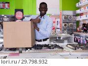 Купить «Male with packagedpurchases in modern household shop», фото № 29798932, снято 21 февраля 2018 г. (c) Яков Филимонов / Фотобанк Лори