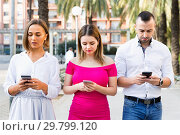Young people are focusing on smartphones during a together walking outdoors. Стоковое фото, фотограф Яков Филимонов / Фотобанк Лори