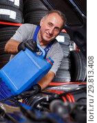 Купить «Mechanic engaged in replacement of engine oil», фото № 29813408, снято 4 сентября 2018 г. (c) Яков Филимонов / Фотобанк Лори