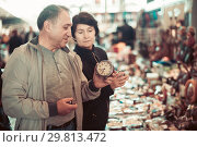 Купить «Adult man and woman are looking antiquariat at the market of old things», фото № 29813472, снято 23 октября 2017 г. (c) Яков Филимонов / Фотобанк Лори