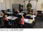 Купить «School kids raising hand in classroom of elementary school», фото № 29820004, снято 10 ноября 2018 г. (c) Wavebreak Media / Фотобанк Лори