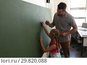 Купить «Side view of schoolgirl with math teacher writing on chalk board in classroom», фото № 29820088, снято 10 ноября 2018 г. (c) Wavebreak Media / Фотобанк Лори