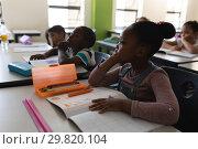 Купить «Side view of schoolkids studying and sitting at desk in classroom», фото № 29820104, снято 10 ноября 2018 г. (c) Wavebreak Media / Фотобанк Лори