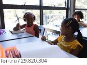Купить «Happy schoolkids talking with each other at desk in classroom», фото № 29820304, снято 10 ноября 2018 г. (c) Wavebreak Media / Фотобанк Лори