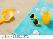 Купить «sunglasses, sand toys and juice on beach towel», фото № 29820572, снято 27 июня 2018 г. (c) Syda Productions / Фотобанк Лори