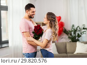 Купить «happy couple with bunch of flowers hugging at home», фото № 29820576, снято 30 ноября 2018 г. (c) Syda Productions / Фотобанк Лори