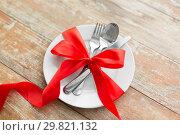 Купить «cutlery tied with red ribbon on set of plates», фото № 29821132, снято 9 февраля 2018 г. (c) Syda Productions / Фотобанк Лори