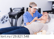 Купить «Cosmetician examining face skin of girl», фото № 29821548, снято 16 марта 2018 г. (c) Яков Филимонов / Фотобанк Лори