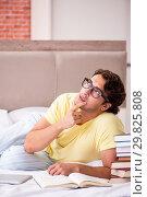 Купить «Young student studying in bed for exams», фото № 29825808, снято 17 сентября 2018 г. (c) Elnur / Фотобанк Лори