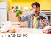 Купить «Young man calculating expences for vegetables in kitchen», фото № 29826100, снято 3 августа 2018 г. (c) Elnur / Фотобанк Лори