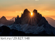 The sun rises exactly in between the crags of the Tre Cime di Lavaredo. This effect occurs only few days per year, exactly during winter solstice days... Стоковое фото, фотограф ClickAlps / age Fotostock / Фотобанк Лори