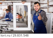 Купить «hardworking professional labours with finished PVC profiles and windows», фото № 29831548, снято 30 марта 2017 г. (c) Яков Филимонов / Фотобанк Лори