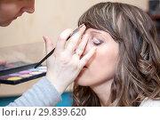 Купить «Female hands applying eye shadows on face skin, close up view at head of curly haired woman», фото № 29839620, снято 20 апреля 2012 г. (c) Кекяляйнен Андрей / Фотобанк Лори