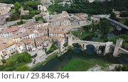 Купить «Aerial view of historic centre of Besalu with Romanesque bridge over Fluvia river, Catalonia, Spain», видеоролик № 29848764, снято 12 июня 2018 г. (c) Яков Филимонов / Фотобанк Лори