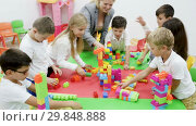 Купить «Cute schoolchildren creating constructions from toy blocks with teacher in classroom», видеоролик № 29848888, снято 18 декабря 2018 г. (c) Яков Филимонов / Фотобанк Лори