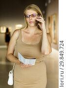 Купить «Woman with brochure looking at exposition», фото № 29849724, снято 22 сентября 2018 г. (c) Яков Филимонов / Фотобанк Лори