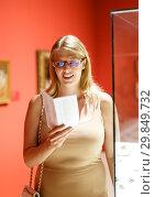 Купить «Woman with glasses visiting museum of arts», фото № 29849732, снято 22 сентября 2018 г. (c) Яков Филимонов / Фотобанк Лори